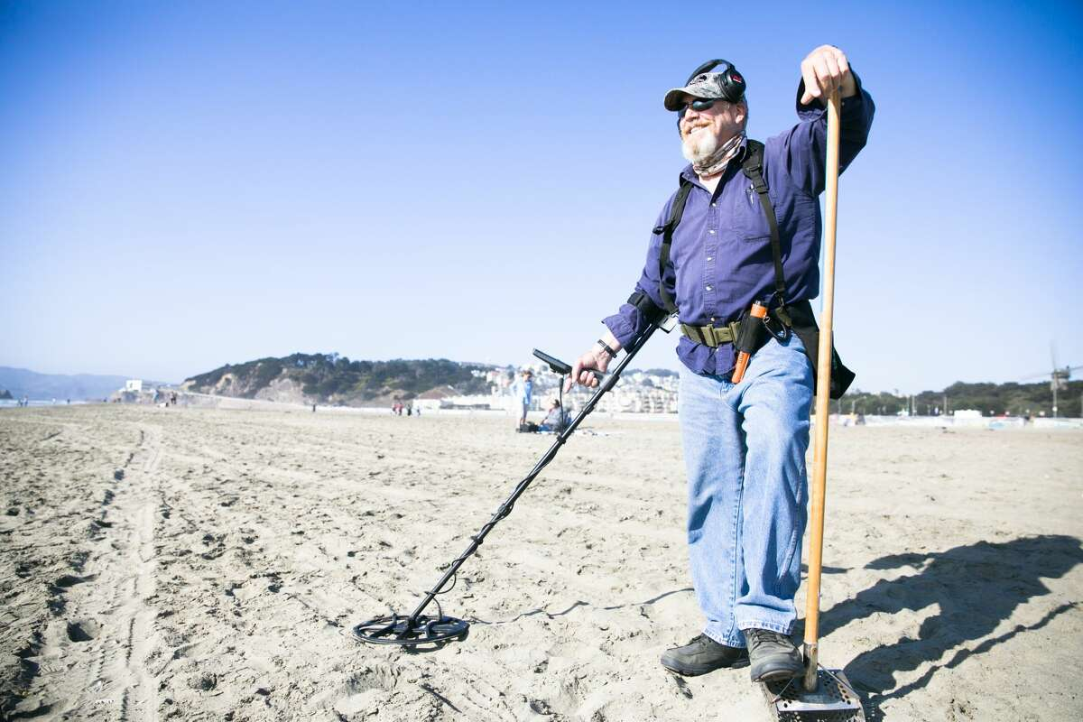Metal detectorist Marshall Smith poses for a photograph while recreational metal detecting on a trip to Ocean Beach in San Francisco on Aug. 26, 2021. Smith is the San Francisco liaison for the Ring Finders, a directory of independent metal detecting specialists around the world who help people find lost jewelry.
