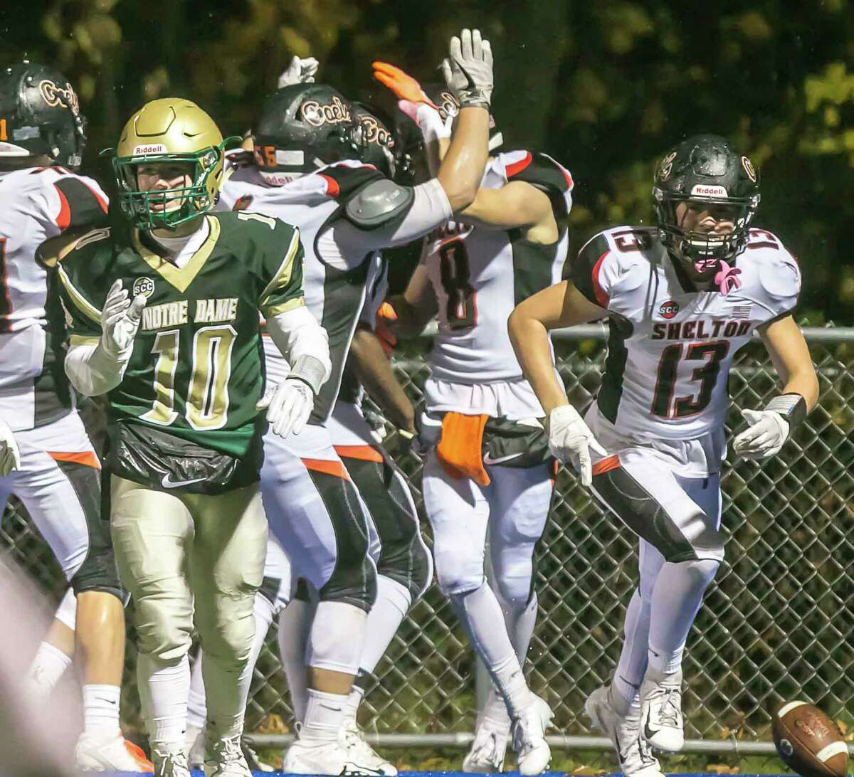 Shelton's David Yakowicz (8) and his teammates celebrate their opening kickoff touchdown against Notre Dame-West Haven.