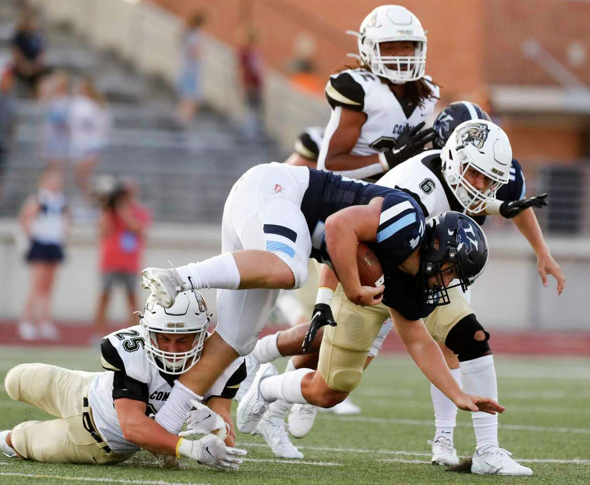 Kingwood running back Nick Bernell (24) is tackled by Conroe outside linebacker Austin Shaw (25) during the first quarter of a non-district high school football game at Turner Stadium, Thursday, Sept. 2, 2021, in Humble.