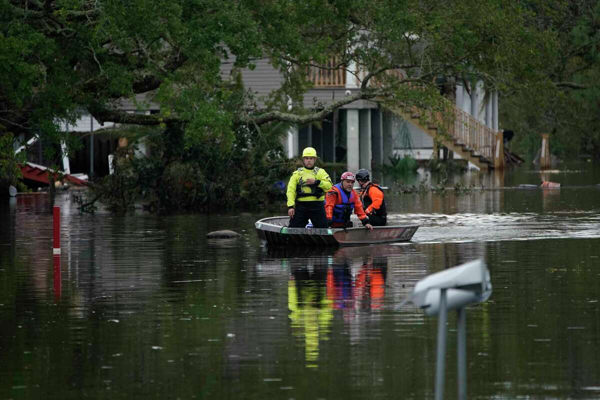 Animal rescue officials drive a boat down a flooded street in the aftermath of Hurricane Ida in Lafitte, La.