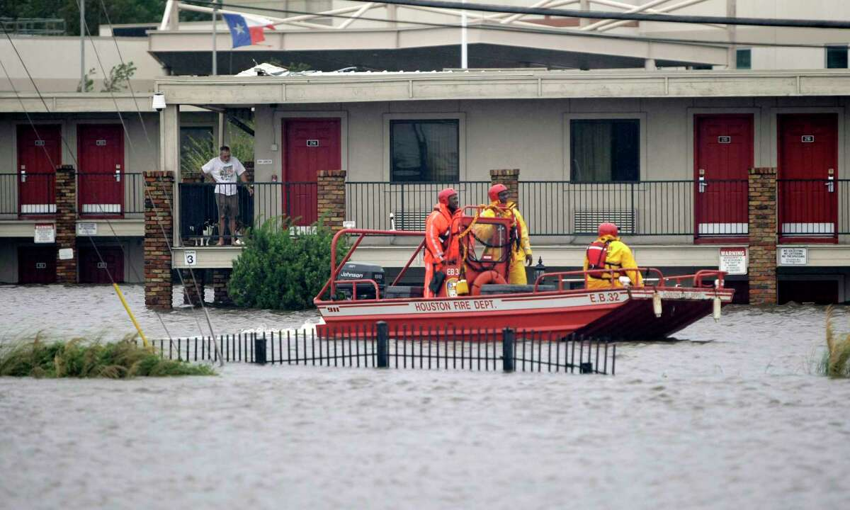 Houston Fire Department members in a rescue boat look for people in need of rescue at the Interstate Motor Lodge off of I-10 and Uvalde, as several people staying there declined to be taken away after Hurricane Ike moved out of the area, leaving several areas, including this one on Greens Bayou flooded, Saturday, September 13, 2008.