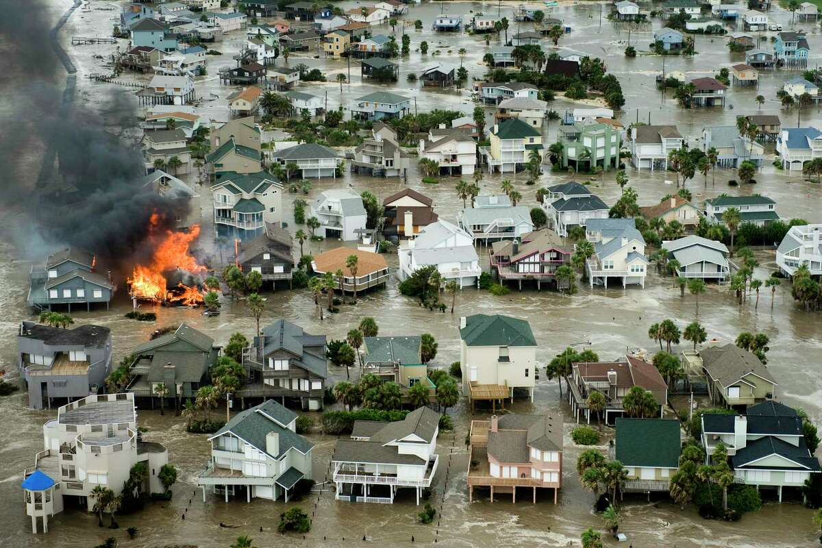 A house is totally engulfed in flames as floodwaters and crashing waves inundated beach homes on Galveston Island as Hurricane Ike approaches the Texas Gulf Coast, Friday, Sept. 12, 2008. ( Smiley N. Pool / Chronicle )
