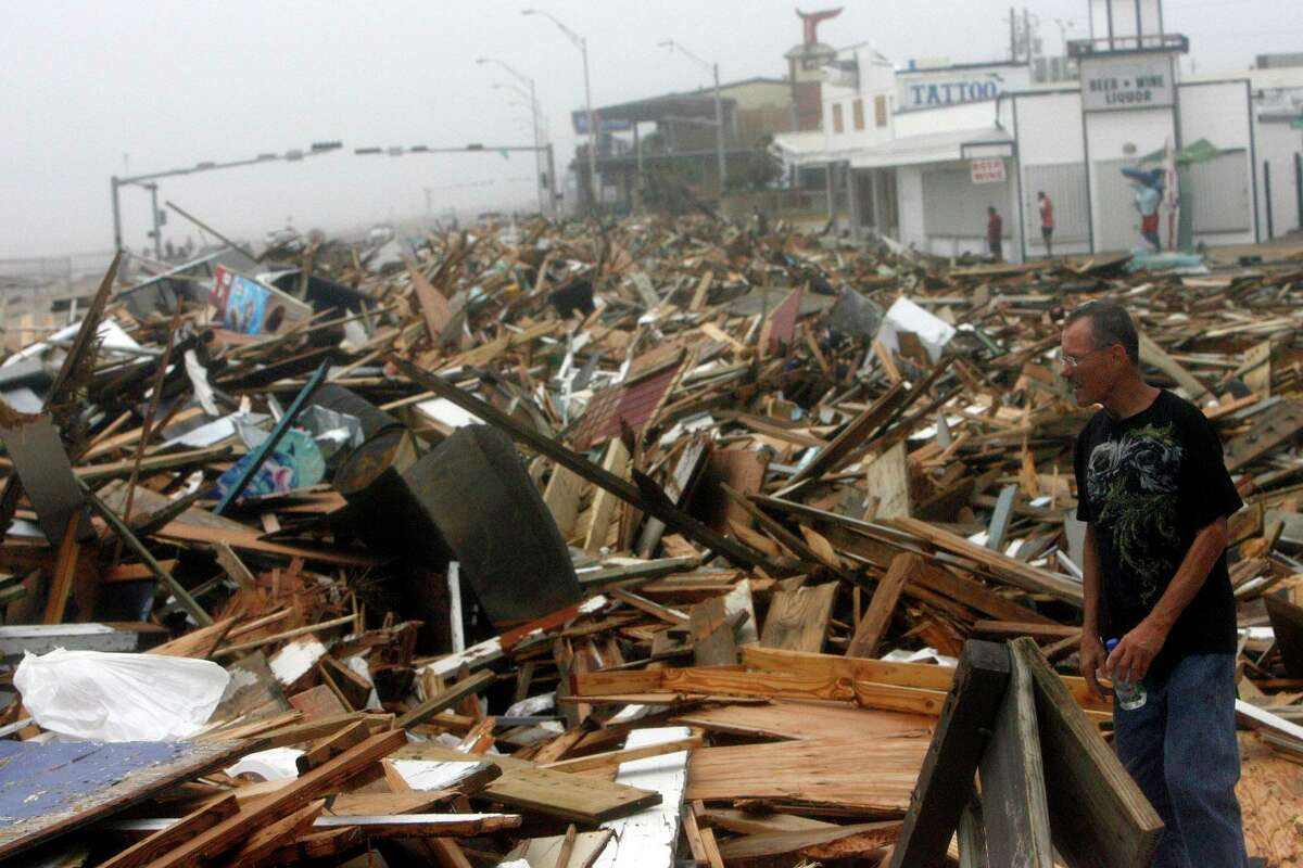 Galveston resident of four years, Gary Simmons walks among the rubble of Murdock's Pier and Hooters left by Hurricane Ike along Seawall Blvd. Saturday, Sept. 13, 2008.