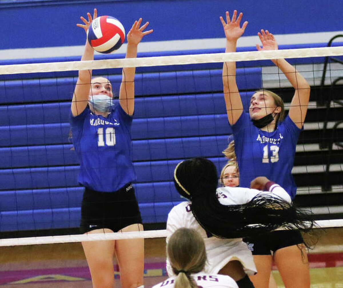 Marquette Catholic's Abby Williams (10) gets a block alongside teammate Olivia Ellebracht (13) in a match vs. EA-WR at the Roxana Tourney on Aug. 23 in Roxana. On Thursday, the Explorers beat Greenville to improve their record to 8-1.