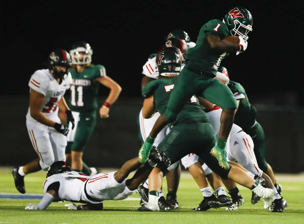 The Woodlands running back JoBarre Reed (1) leaps over a Langham Creek defensive back Alejandro Vasquez (18) on his way to the game-winning 41-yard touchdown during the fourth quarter of a non-district high school football game at Woodforest Bank Stadium, Thursday, Aug. 26, 2021, in Shenandoah.
