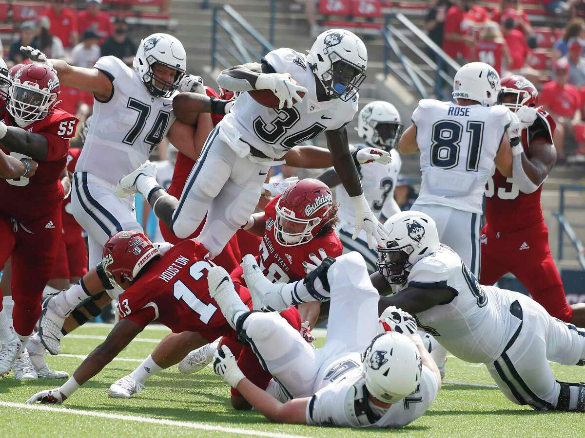 UConn running back Kevin Mensah (34) goes up for a short gain against Fresno State on Saturday.