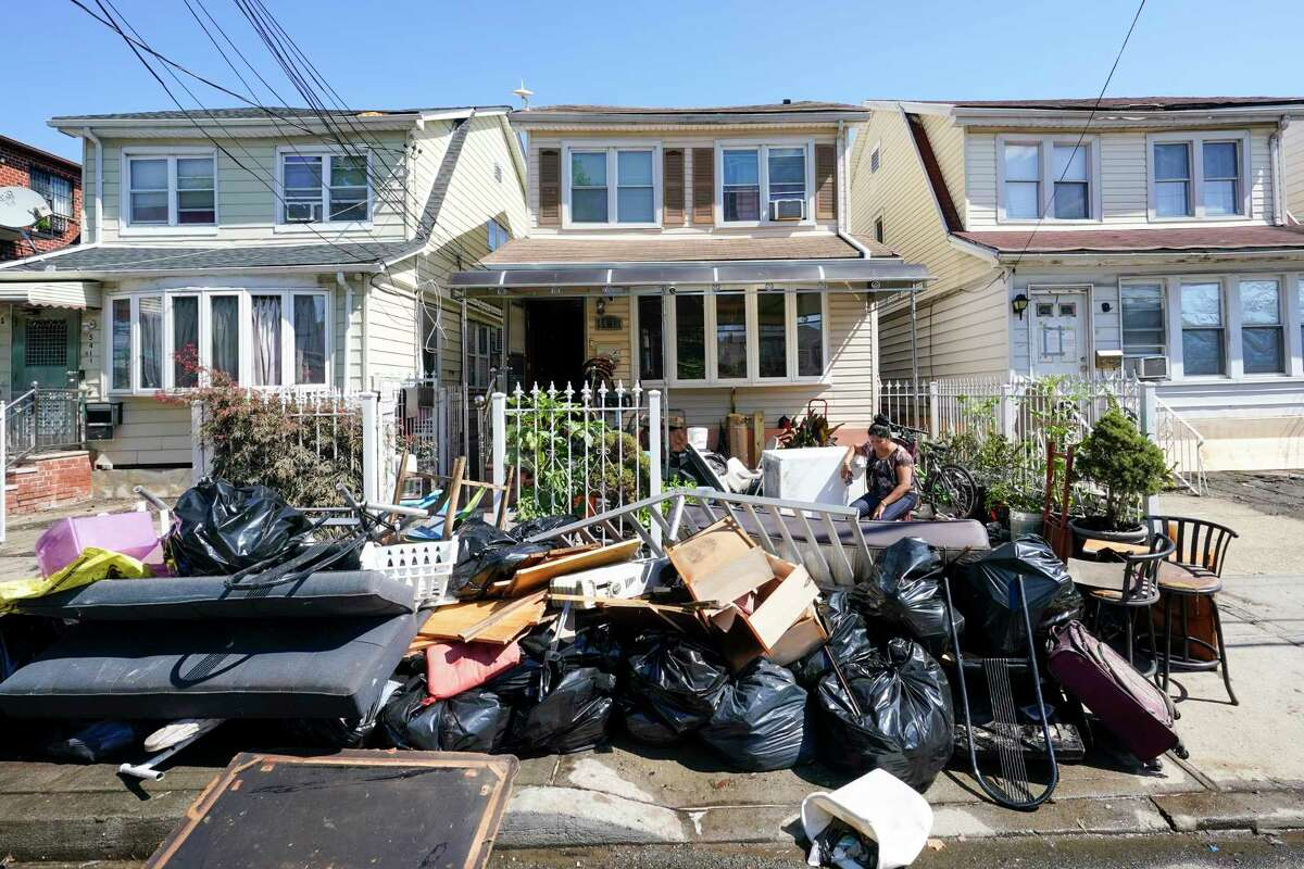 A resident of 153rd St. in the Flushing neighborhood of the Queens borough of New York sits outside her home with her water logged belongings, Thursday, Sept. 2, 2021, in New York. The remnants of Hurricane Ida dumped historic rain over New York City, with several deaths linked to flooding in the region as basement apartments suddenly filled with water and freeways and boulevards turned into rivers, submerging cars.