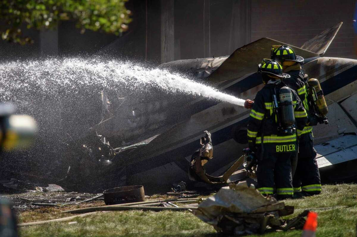 Firefighters work near the wreckage of a Cessna Citation 560X aircraft that crashed into a building at the manufacturing company Trumpf Inc. in Farmington, Conn., and caught fire