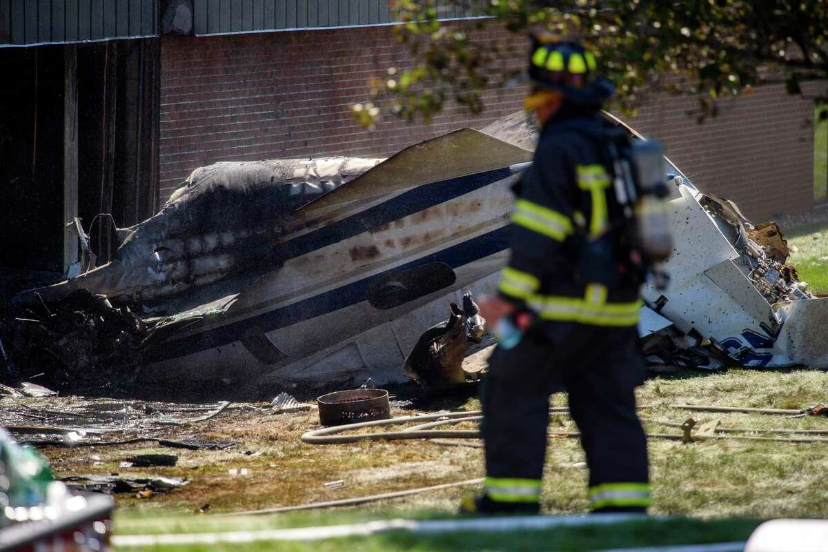 A firefighter near the wreckage of a Cessna Citation 560X aircraft that crashed into a building at the manufacturing company Trumpf Inc. in Farmington, Conn., and caught fire Thursday, Sept. 2, 2021, after taking off from nearby Robertson Airport in Plainville, Conn. The small jet crashed shortly after taking off, killing all four people aboard, officials said. (Mark Mirko/Hartford Courant via AP)