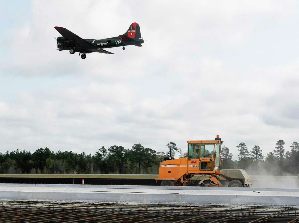 A B-17 Flying Fortress flies over construction equipment as a taxiway is worked on at Conroe-North Houston Regional Airport, Thursday, March 25, 2021, in Conroe. Since 2011, operations at the airport have increased 50 percent, according to Airport Director James Brown.