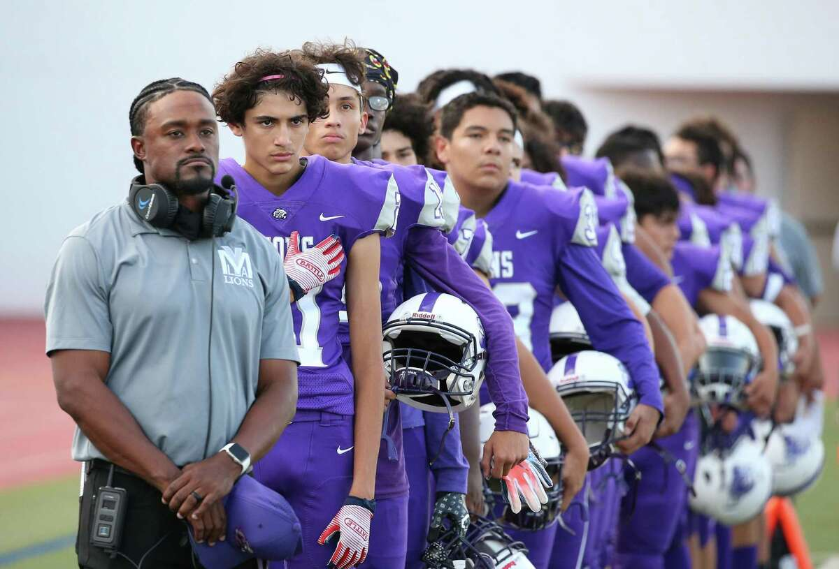 YMLA head coach Tony Green stands with his team during the National Anthem. YMLA defeated Luling 6-2 on Thursday, Sept. 2, 2021 at Alamo Stadium.