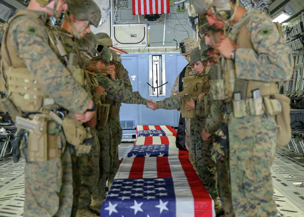 In this image provided by the U.S. Marine Corps, U.S. service members assigned to Joint Task Force-Crisis Response, who are serving as pallbearers, pause onboard a U.S. Air Force C17A globemaster III, Friday, Aug. 27, 2021, during a ramp ceremony for the service members killed in action at Hamid Karzai International Airport in Kabul, Afghanistan. (U.S. Marine Corps via AP)