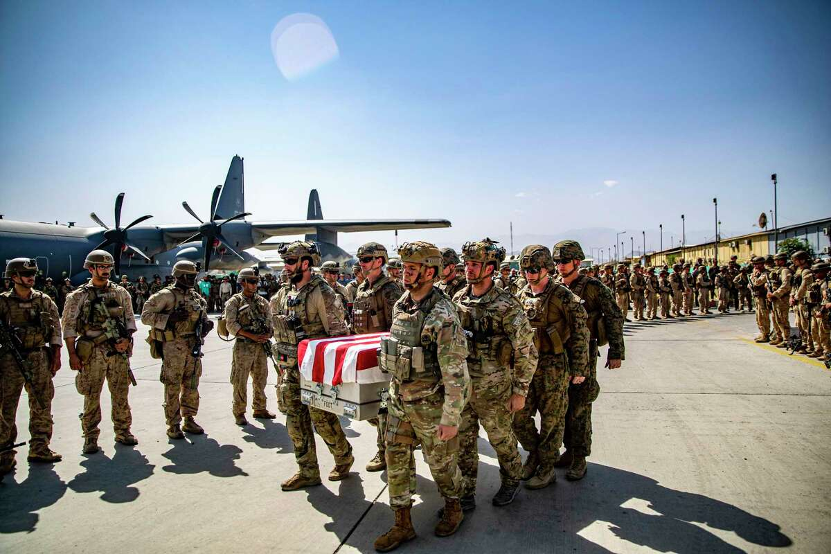 In this image provided by the US Marine Corps, the US servicemen assigned to the Joint Task Force-Crisis Response are carrying on Friday, August 27, 2021, servicemen killed in action during operations at Hamid Karzai International Airport in Kabul , Afghanistan, as the transfer cases are placed on a US Air Force C17A Globemaster III for the return flight to the United States.  (1st Lt. Mark Andries / US Marine Corps via AP)