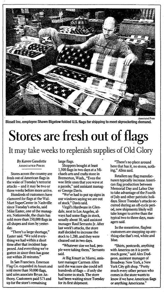 """An S.F. Chronicle article shows a man folding U.S. flags with the headline """"Stores are fresh out of flags."""""""