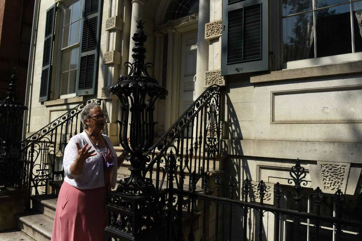 """Kathy Sheehan, city of Troy and Rensselaer County historian, points out some of the architectural details at Hart Cluett Museum, which are featured in the new HBO series """"Gilded Age"""" on Thursday, Aug. 26, 2021, in Troy, N.Y. Sheehan is planning a walking tour for Sept. 11 that will show where """"Gilded Agewas filmed in Troy."""