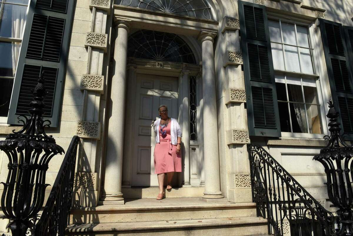 """Kathy Sheehan, city of Troy and Rensselaer County historian, walks out of the Hart Cluett Museum, which is featured in the new HBO series ?""""Gilded Age?• on Thursday, Aug. 26, 2021, in Troy, N.Y. Sheehan is planning a walking tour for Sept. 11 that will show where ?""""Gilded Age?• was filmed in Troy."""