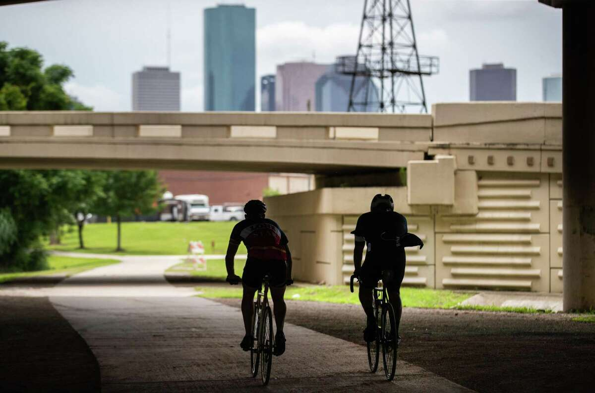 Cyclists silhouetted as they ride on the White Oak Bayou Greenway Trail, Friday, May 21, 2021, in Houston.