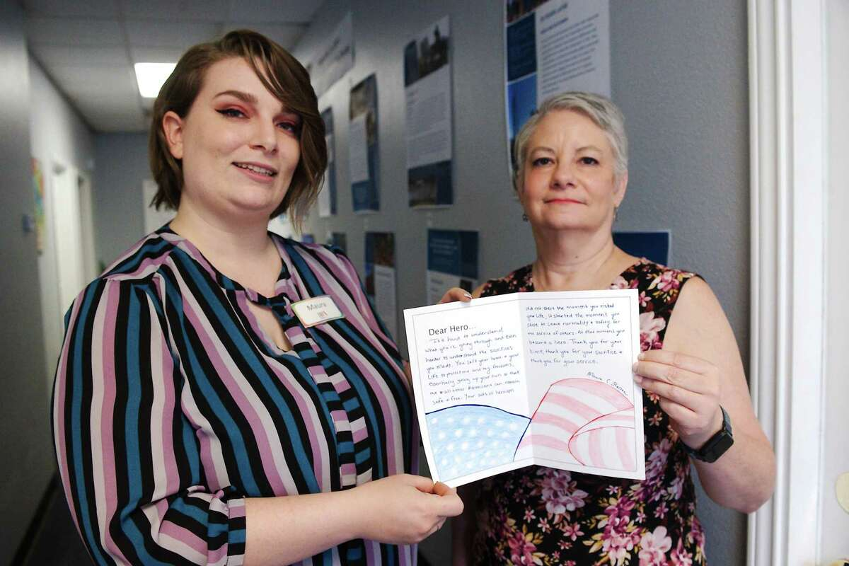 Manvel Public Library clerk Maura Shelton and branch manager Carolynn Waites hold a thank-you card for first responders. Visitors to the library on Sept. 11 will be able to write such letters as part of activities to commemorate the 20th anniversary of the 9/11 terrorist attacks.