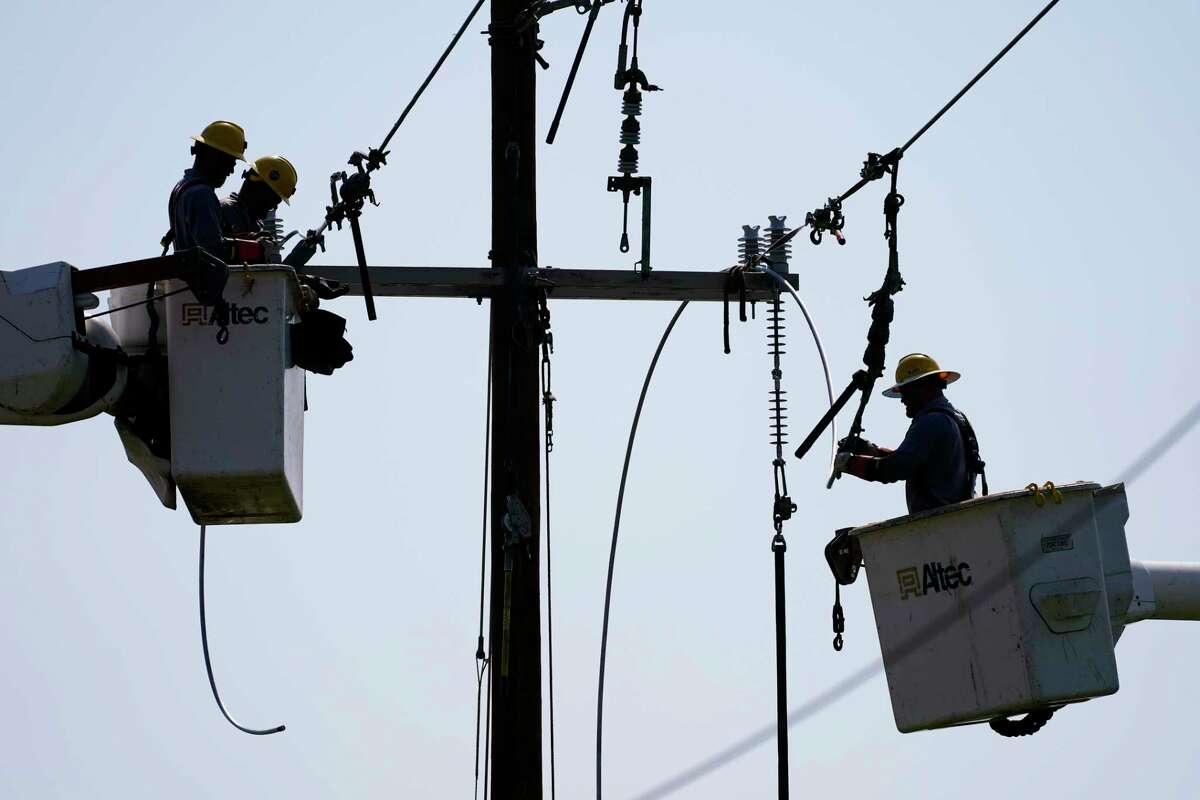 Crews work on power lines that were damaged in the aftermath of Hurricane Ida, Friday, Sept. 3, 2021, in LaPlace, La.