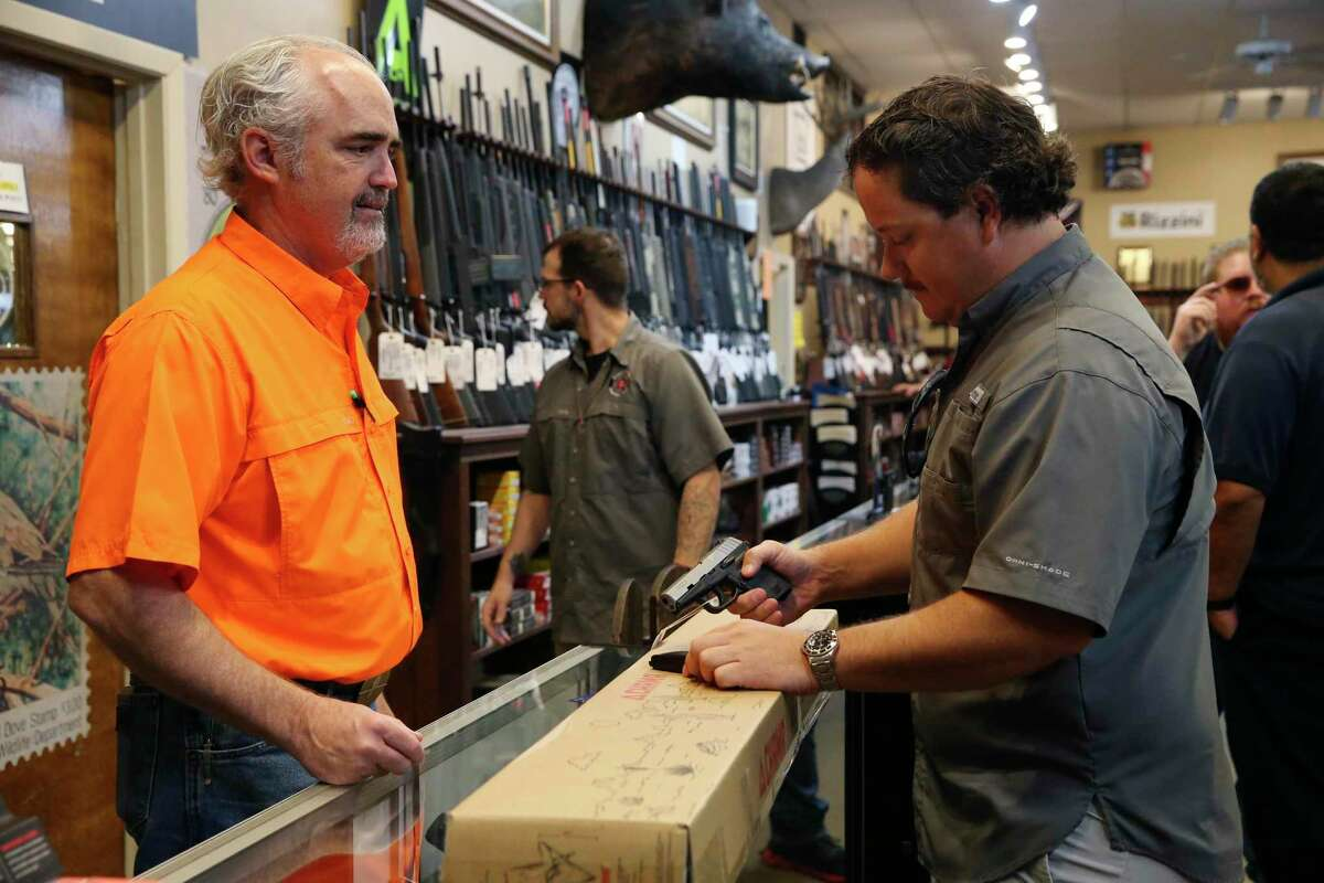 """Ranger Firearms owner Edward E. DeWees III shows a handgun to Austin Evans, Friday, Aug. 3, 2021. Texas' """"constitutional carry"""" law took effect Wednesday, allowing adults over 21 without criminal backgrounds to carry handguns without a license."""