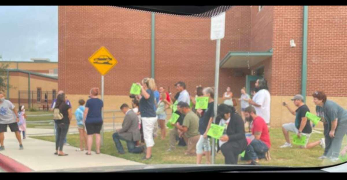 An anti-mask group crowded outside of Cole Elementary School Friday morning.