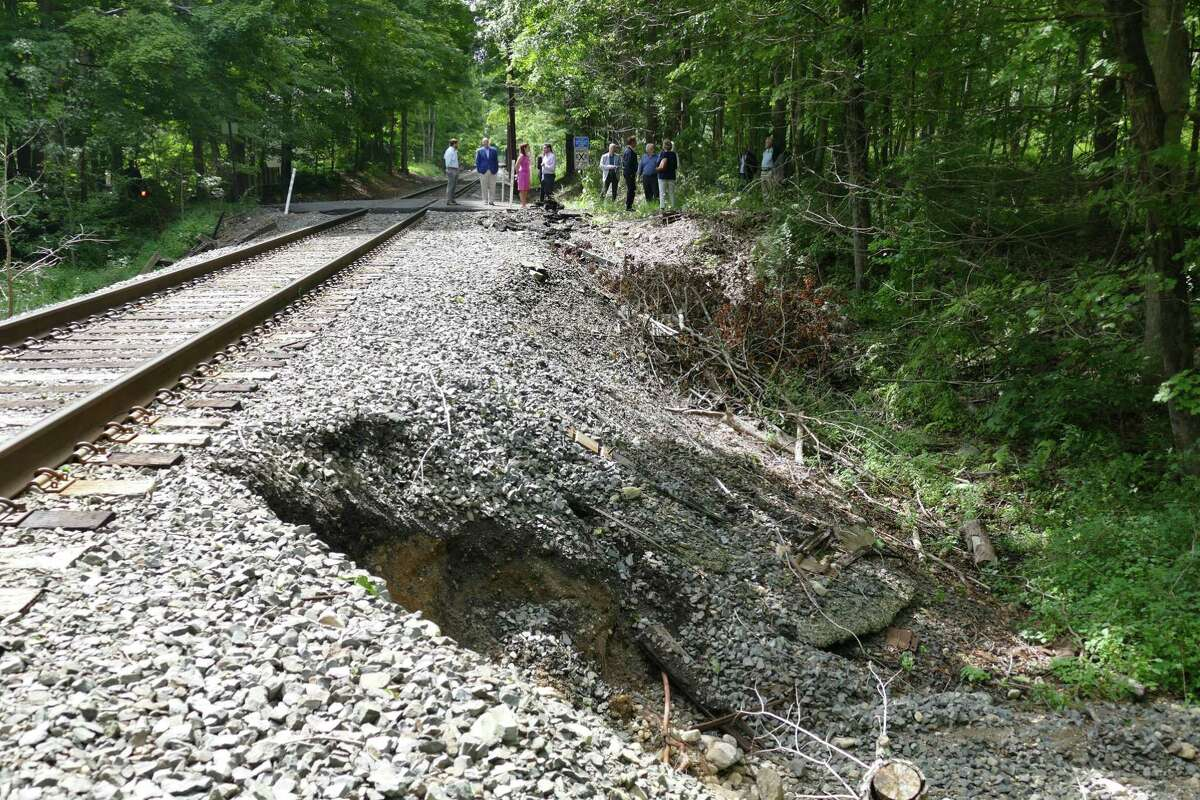 Connecticut officials, including Gov. Ned Lamont, inspect damage to the Danbury branch of the Metro-North Railroad in Redding Friday.