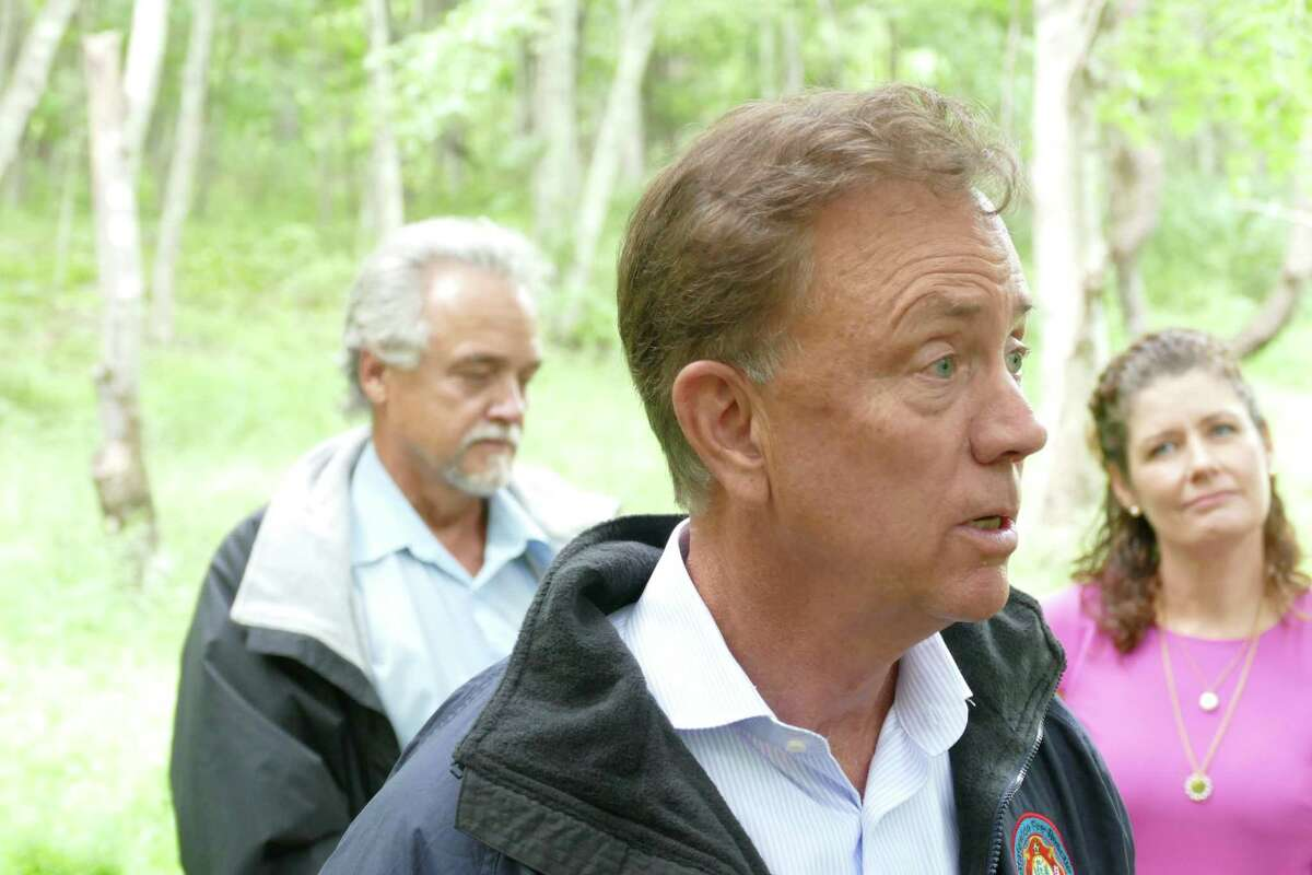 Connecticut Gov. Ned Lamont, flanked by Commissioner Katie Dykes of the Department of Energy and Environmental Protection survey the damage from Ida on Friday, Sept. 3, 2021.