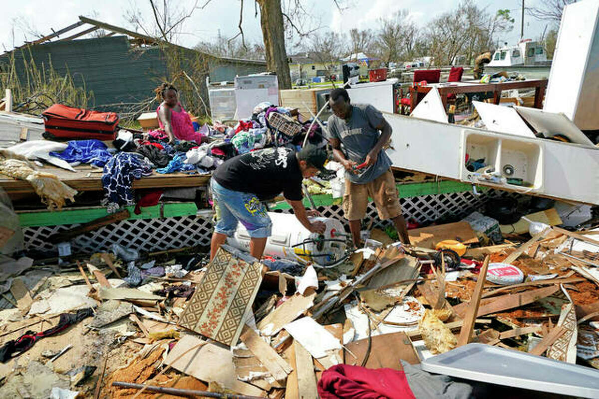 Cruz Palma (left) watches as her son, Jose Duran (center), and husband, Jose Garcia, work to remove a water heater from what is left of their home in the aftermath of Hurricane Ida in Golden Meadow, Louisiana.