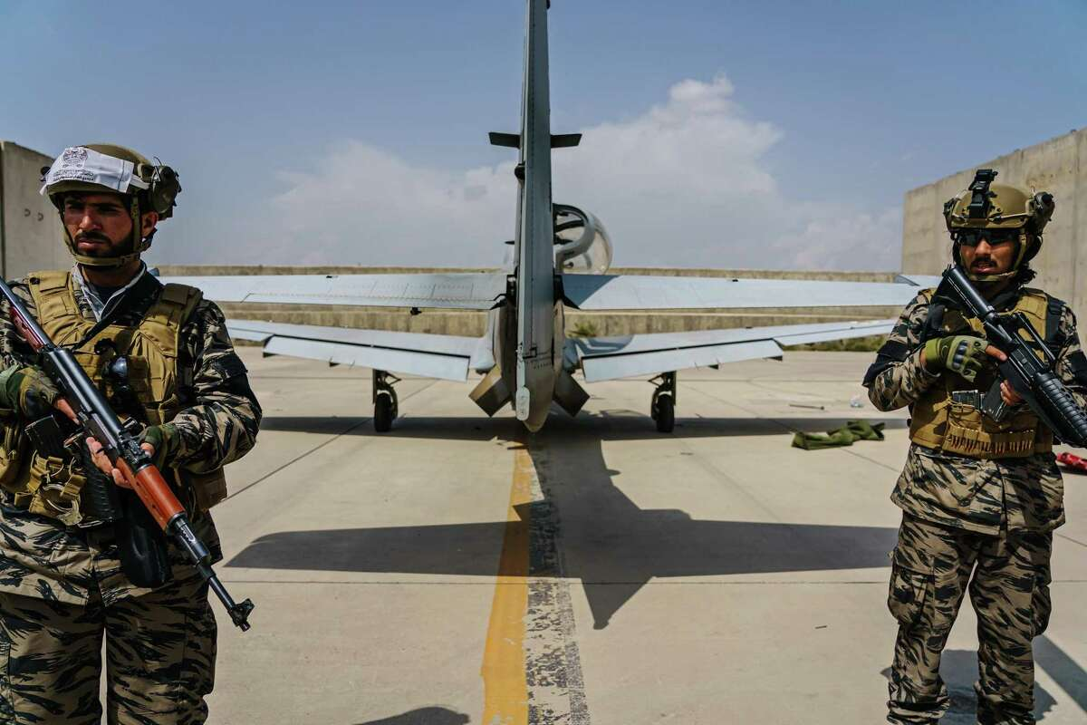Taliban fighters stand guard behind an airplane left by U.S. forces at Hamid Karzai International Airport in Kabul, Afghanistan last month. A reader says the withdrawal was botched, but so was our attempt at nation building.