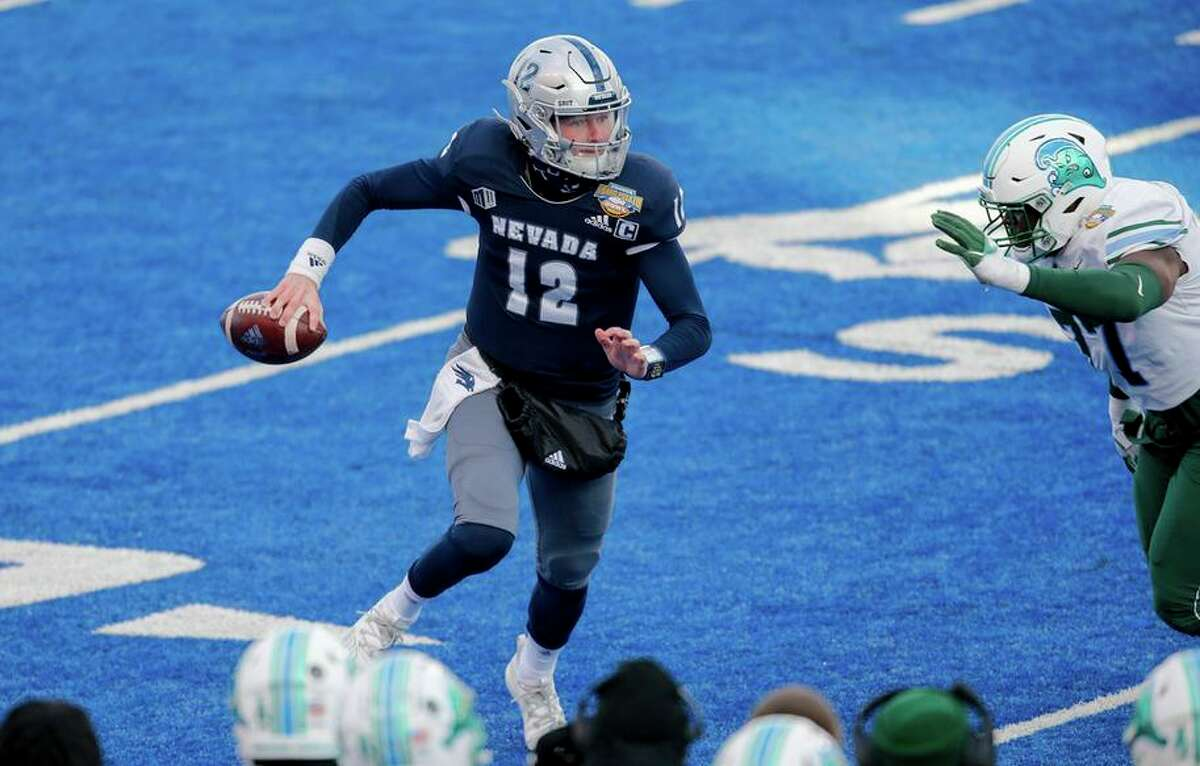 Nevada quarterback Carson Strong (12) looks downfield while Tulane nose tackle Jeffery Johnson (77) pursues during the second half of the Famous Idaho Potato Bowl NCAA college football game Tuesday, Dec. 22, 2020, in Boise, Idaho. Nevada won 38-27. (AP Photo/Steve Conner)