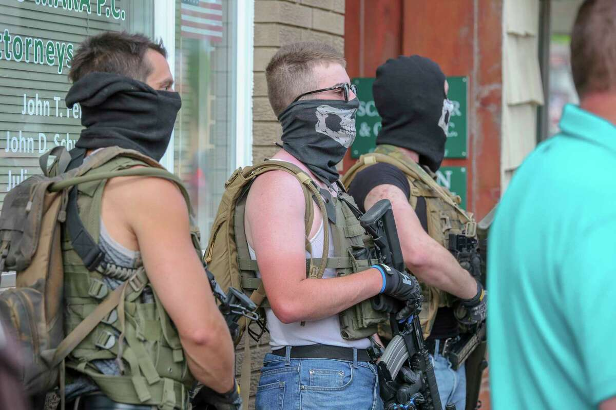 Tensions mount as Thomas Denton, Tristan Webb and Justen Watkins stand by with firearms during a social injustice rally Friday, June 5, 2020.