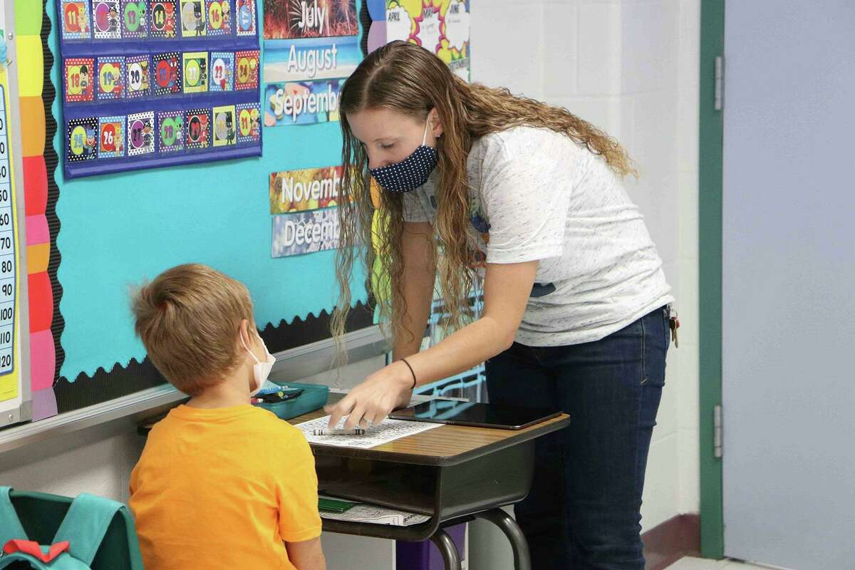 An educator assists a Rustic Oak Elementary School pupil in 2020. After an increase in positive coronavirus cases as well as other indicators, Pearland ISD closed the campus on Sept. 2 with tentative plans to reopen on Sept. 8. On Sept. 2, the district reported 31 cases of COVID among students and five among staff members.