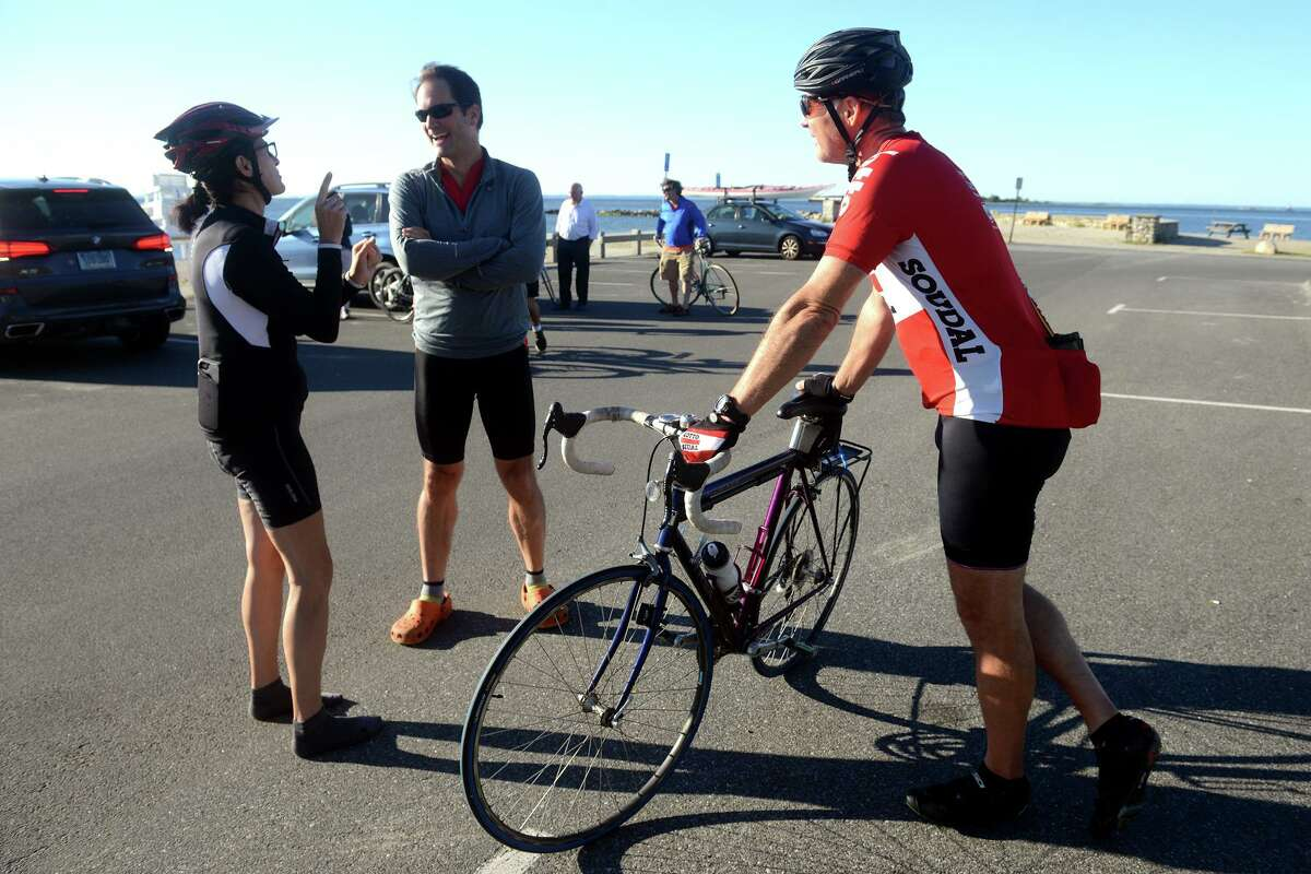 U.S. Rep. Jim Himes, center, speaks with State Rep. Cristin McCarthy-Vahey, of Fairfield, Compo Beach Park, in Westport, Conn. Sept. 3, 3021. Himes was joined by state legislators and community leaders Friday for the first leg of his bicycle tour north to the Massachusetts border.
