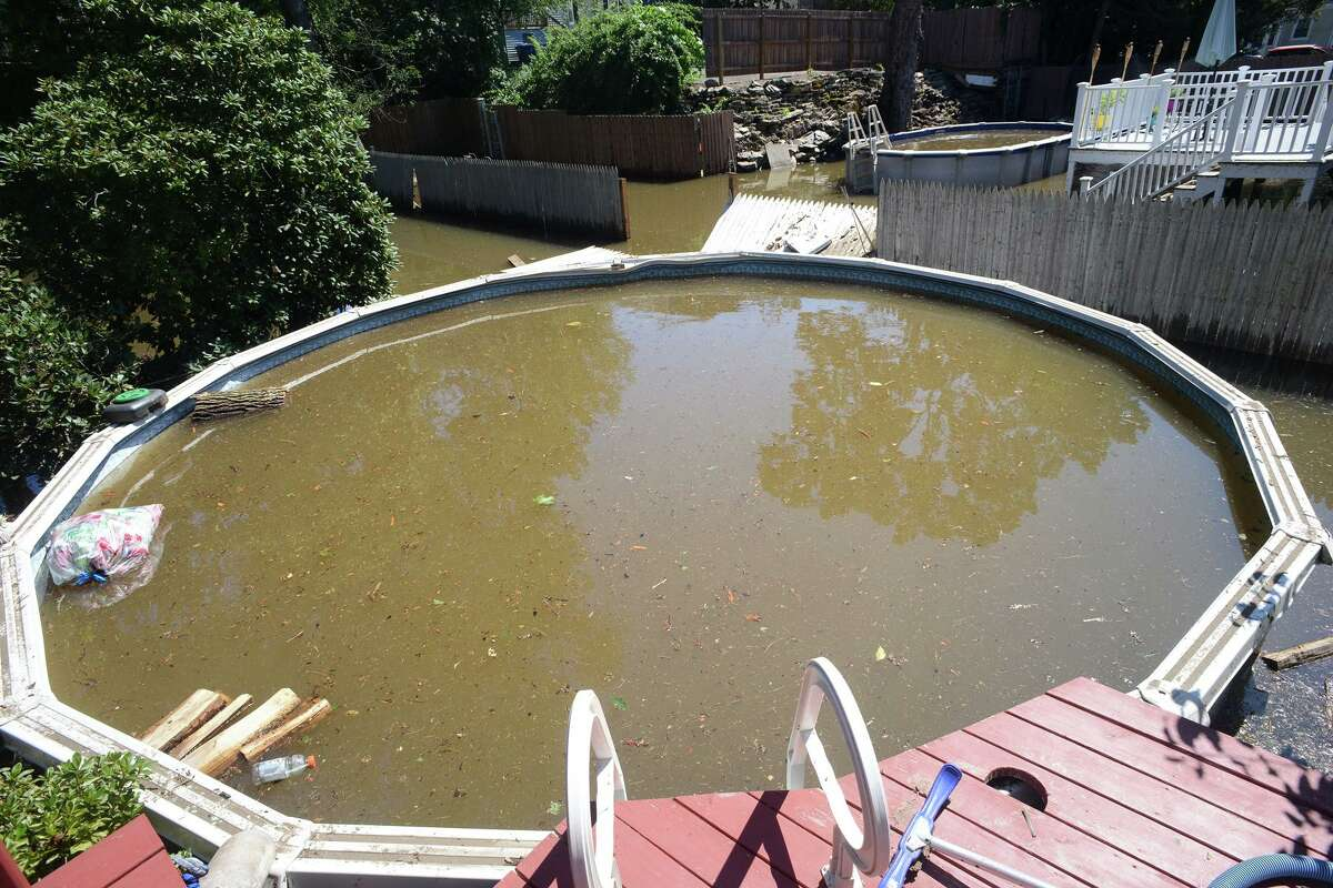 A couple's backyard swimming pool where breached and filled with flood water on Renwick Place, in Bridgeport, Conn. Sept. 2, 2021. The neighborhood was flooded when heavy rains brought in from the remnants of Hurricane Ida caused flooding along the Rooster River.