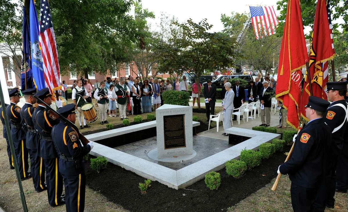 Milford, which lost three residents in the 9/11 attacks, marks the 13th anniversary of the day at a memorial service behind Milford City Hall in downtown Milford, Conn., on Thursday Sept. 11, 2014.