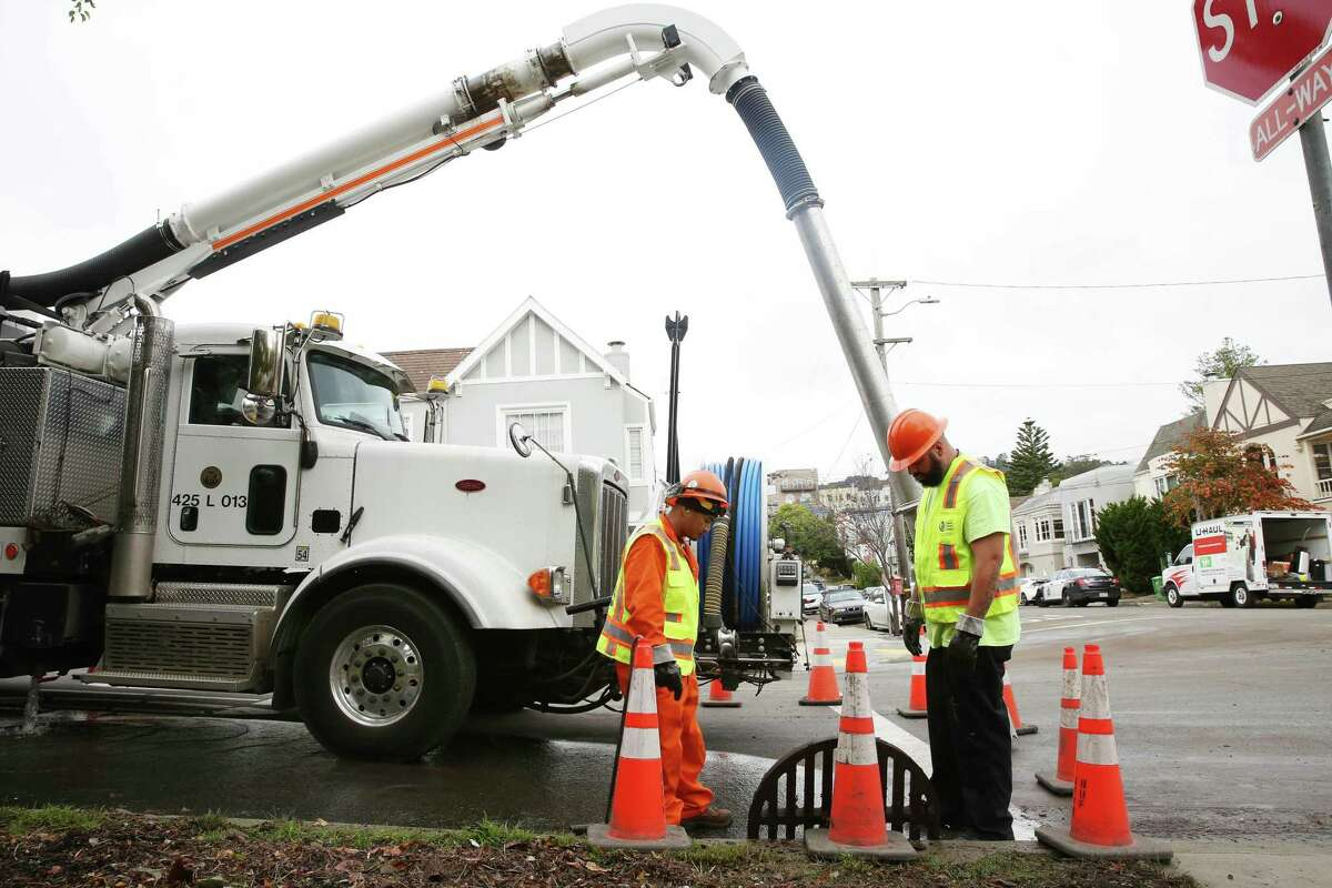 Froilan Tabangcura (l to r) and Joseph Parra, both with the San Francisco Public Utilities Commission, make sure a drain is clear as they work at the flood-prone Wawona Street and 15th Avenue intersection.