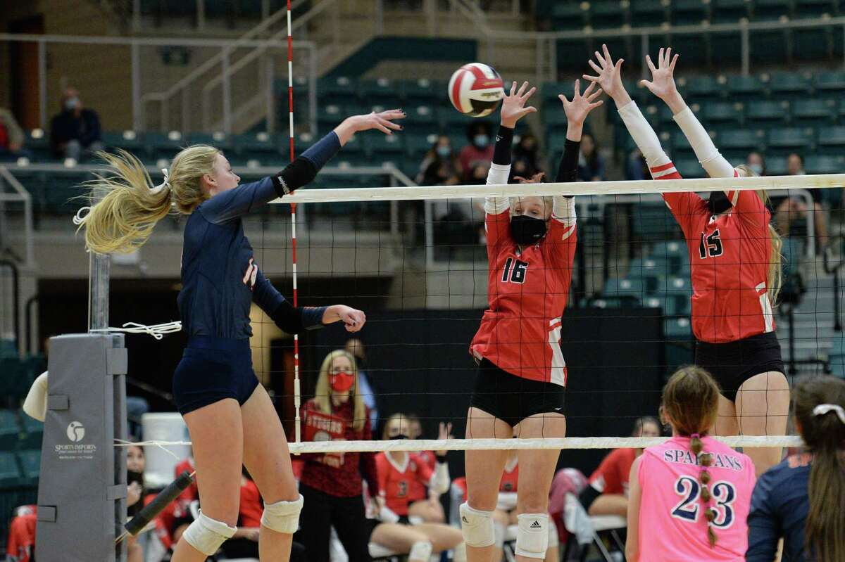 Ally Batenhorst (14) of Seven Lakes attempts a kill shot past Maddie Waak (16) and Jordan Gamble (15) of Katy during the first set of the 6A Region 3 Championship game between the Katy Tigers and the Seven Lakes Spartans on Friday, December 4, 2020 at Leonard Merrell Center, Katy, TX.