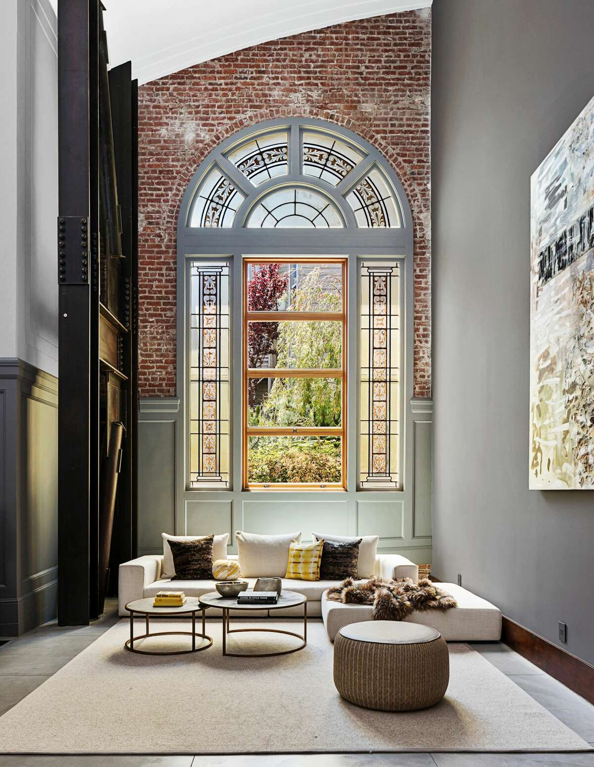 The massive ceilings showcase the tall brick walls embedded with art glass windows.