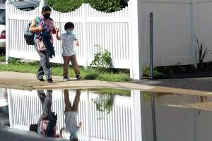 A mother and son walk past a flooded section on North Street in Stamford, Conn., on Friday Sentember 3, 2021. Around the corner at The Wescott, fire crews were still removing water that completely flooded an underground parking garage.