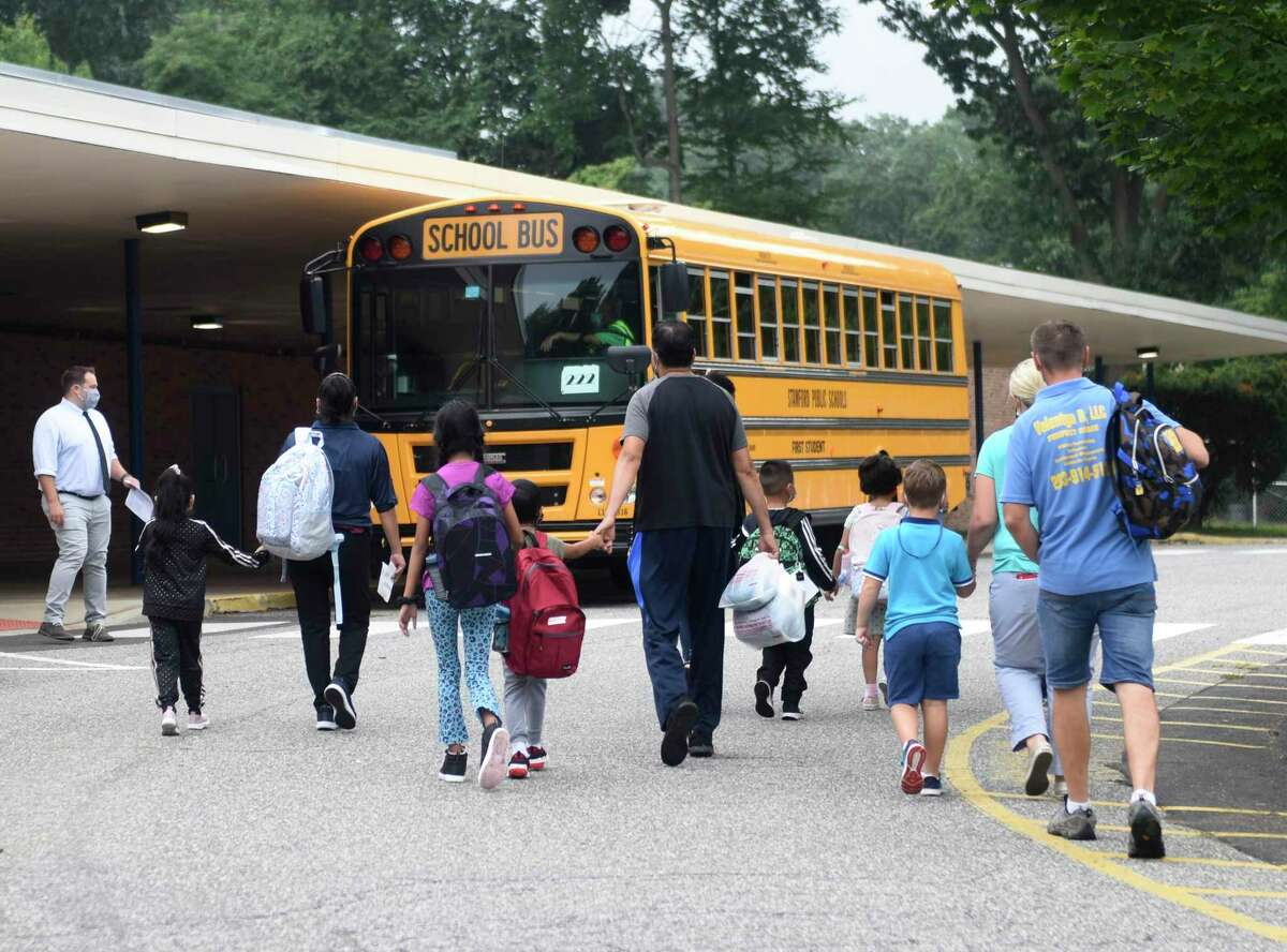 Students arrive on Monday, Aug. 30, 2021, at Newfield Elementary School in Stamford, Conn. With the advent of a new school year, labor officials hope that more parents will reenter the workforce after an extended hiatus during the COVID-19 pandemic while receiving unemployment compensation.