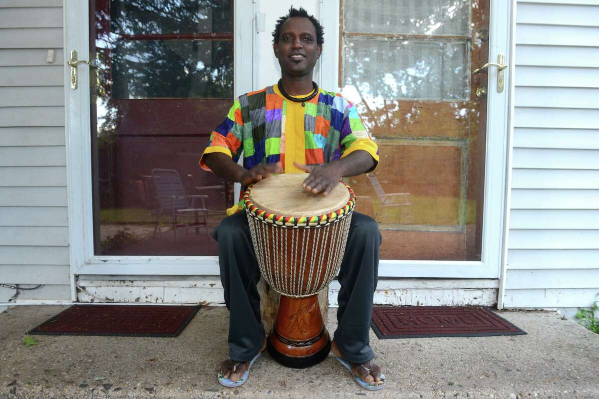 Waly Thiam plays a djembe drum in front of his home in Bridgeport, Conn. Sept. 2, 2021. Thiam recently made a return trip to his home village in Senegal to help work on construction of a new medical facility.