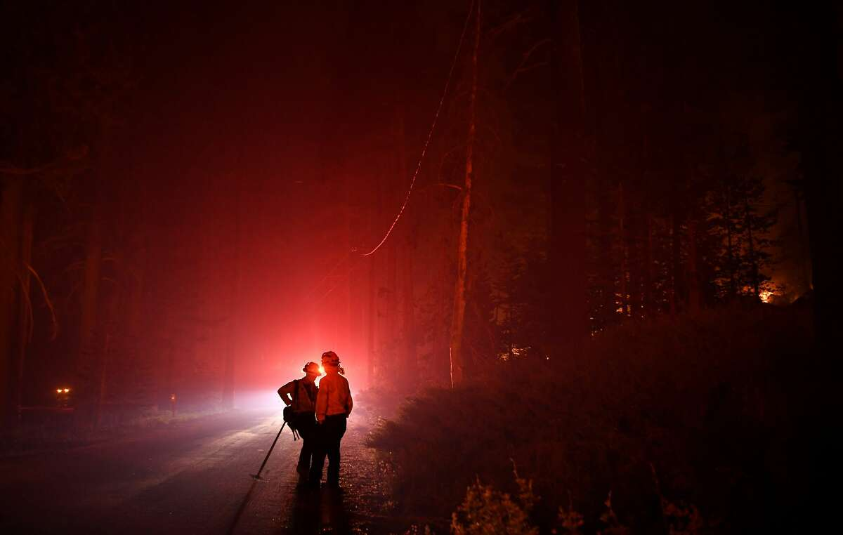 Firefighters take a break along Highway 50 as the Caldor Fire burns near Lake Tahoe on Tuesday.