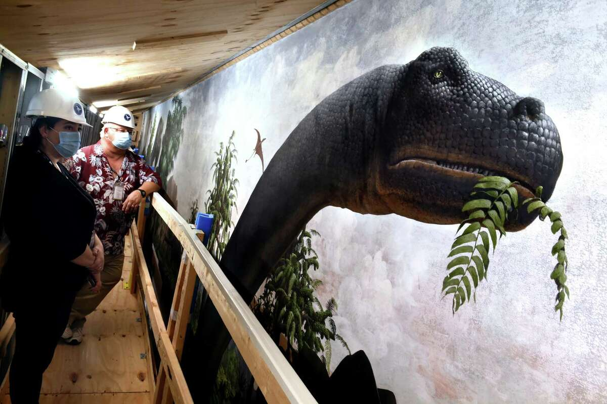Natural History Conservator Mariana Di Giacomo, left, and Tim White, director of collections and research, stand on a walkway next to the head of a Brontosaurus on the Age of Reptiles mural painted by Rudolph Zallinger at the Yale Peabody Museum of Natural History in New Haven Aug. 30, 2021. The mural is encased while construction proceeds at the museum.