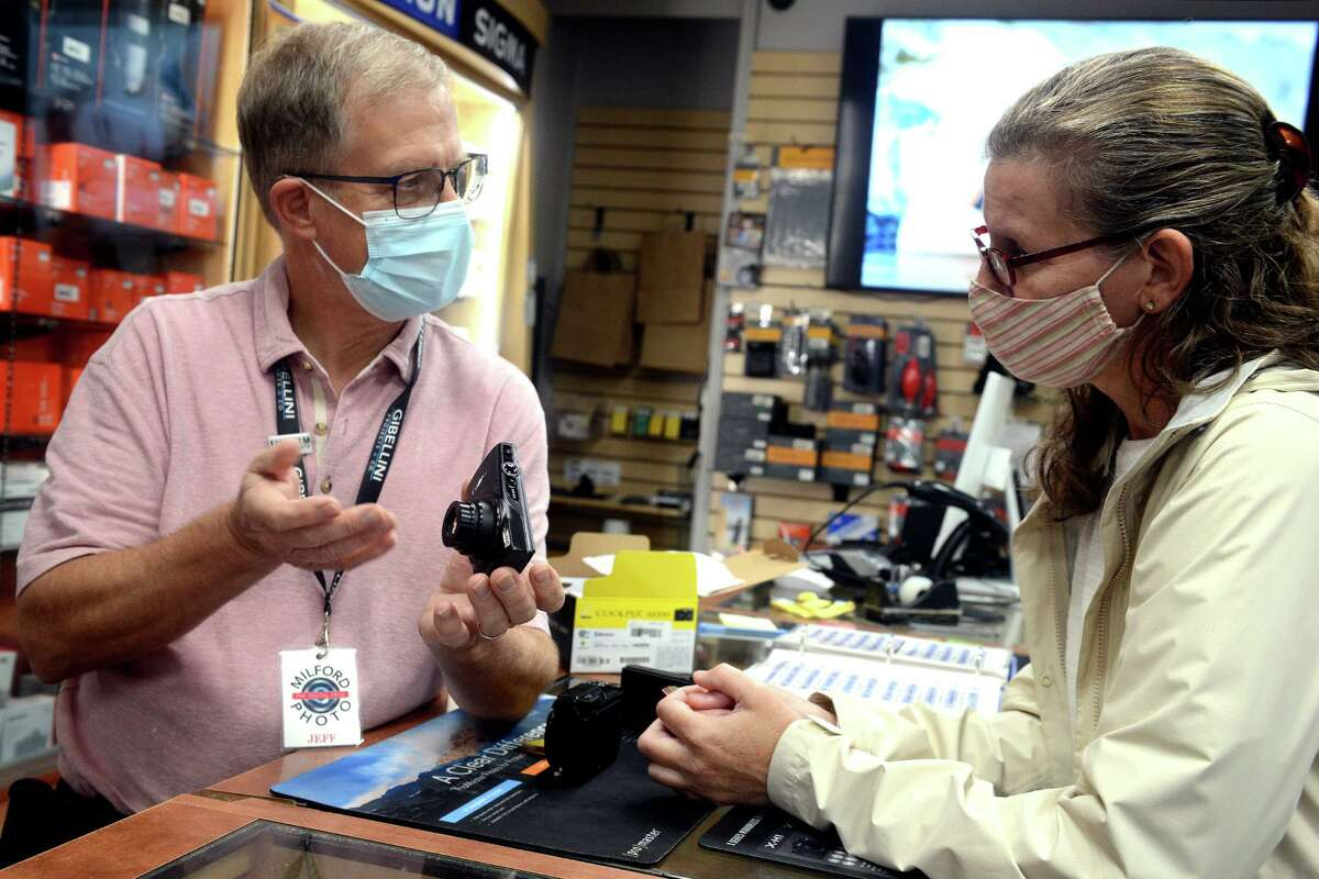 Sales associate Jeff Scholl assists Dawn Tischbein, of Killingworth, as she shops for a digital camera at Milford Photo in Milford on Wednesday.