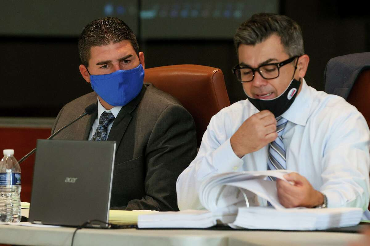 Former San Antonio Police Detective Detective Daniel Pue, left, watches his attorney, Ricardo Garcia, question a witness on Wednesday, Sept. 1, 2021, during an arbitration hearing to determine whether he will be reinstated. Officials say Pue broke into a woman's apartment and hours later punched her in the face during an argument outside his home.