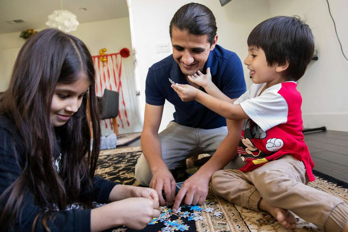 Mr. Sultani spends time playing with his children Uzma, 7, (left) and Edris, 3, at their home in Milpitas, Calif. Tuesday, August 31, 2021. Sultani worked for the U.S. as a translator for the U.S. government, and would be a target of the Taliban. He, his wife and 7-year old daughter are green card holders, and their 3-year old son is a U.S. Citizen. They are residents of Milpitas, but travelled to Afghanistan in June, in part to help facilitate visa applications for family. He received instructions from the U.S. Department of State to go to the Kabul Airport, but the road was impassable due to roadblocks and traffic, and they had to turn back. The following day they approached again, but their daughter was lost in the crowd for about an hour. The next day, they finally made it past the airport gates after being beaten by the Taliban.