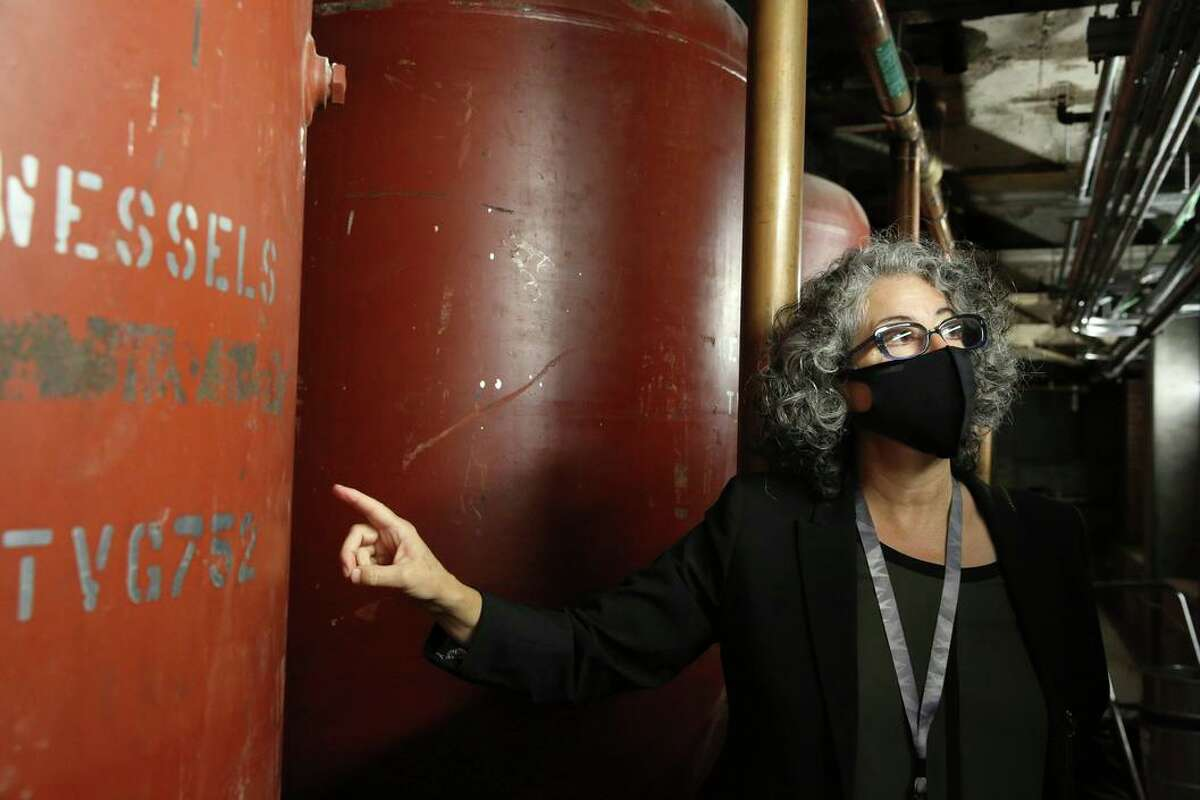 Patty Solis, lead designer, shows daisy-chained water tanks in the basement at the new San Francisco Animal Care & Control center.