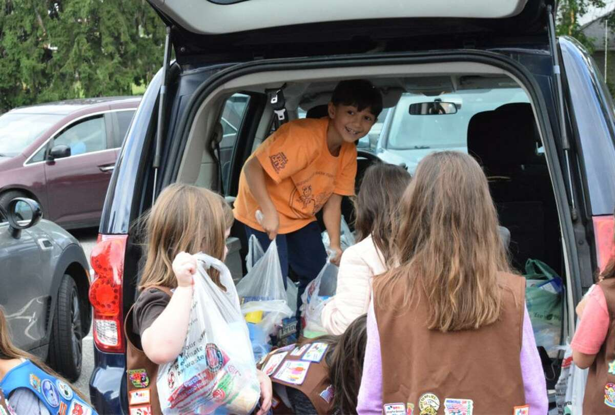 Participants load up a van with food at a prior year's Walk a Mile for a Meal event