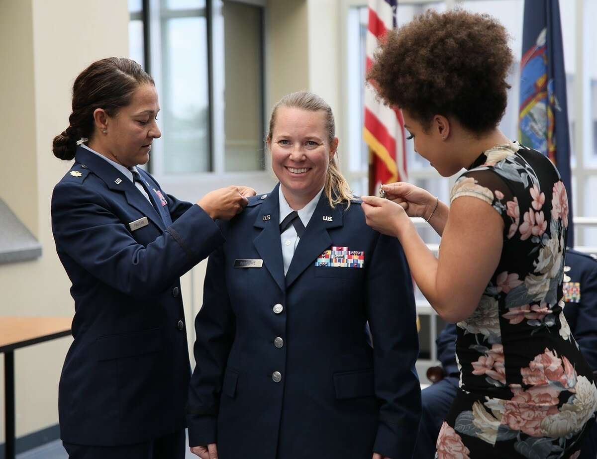 A fellow officer and a niece pin colonel rank insignias on Michelle Buonome during a promotion ceremony in Latham.