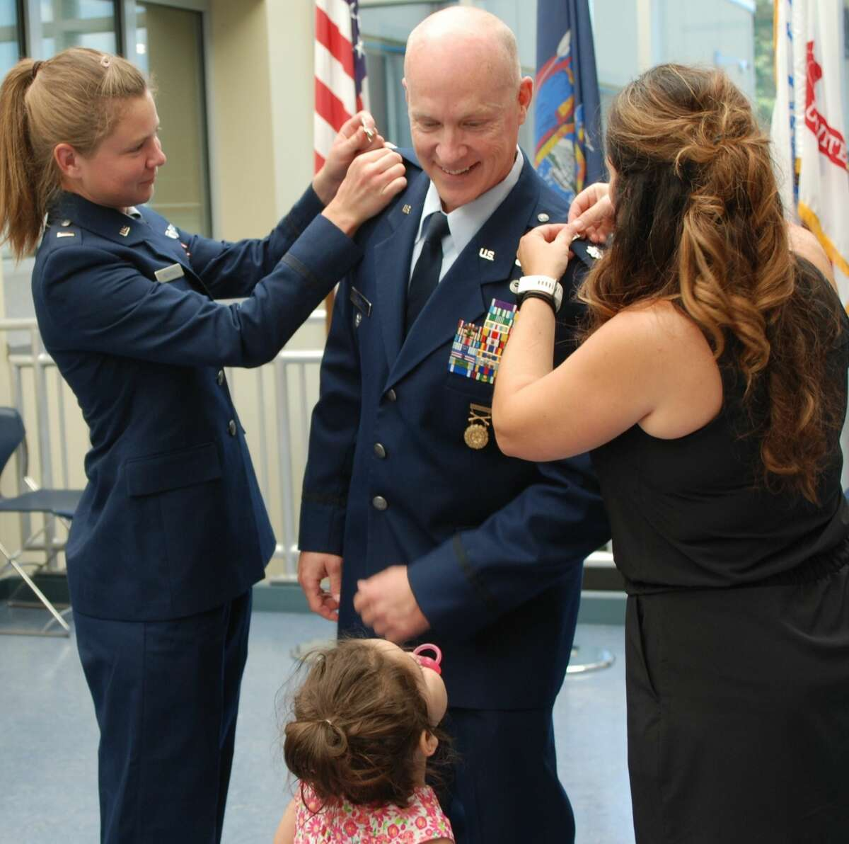 Niece Air Force 1st Lt. Amanda Underhill and fiancée Janelle Fayette pin colonel rank insignias on Eric Underhill during a ceremony in Latham.